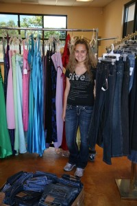 Young entrepreneur — Allyson Ahlstrom stands in front of racks of donated clothing at her temporary Threads for Teens store located at the intersection of Denbeste Court and Conde Lane. - Photo by Lynda Browning